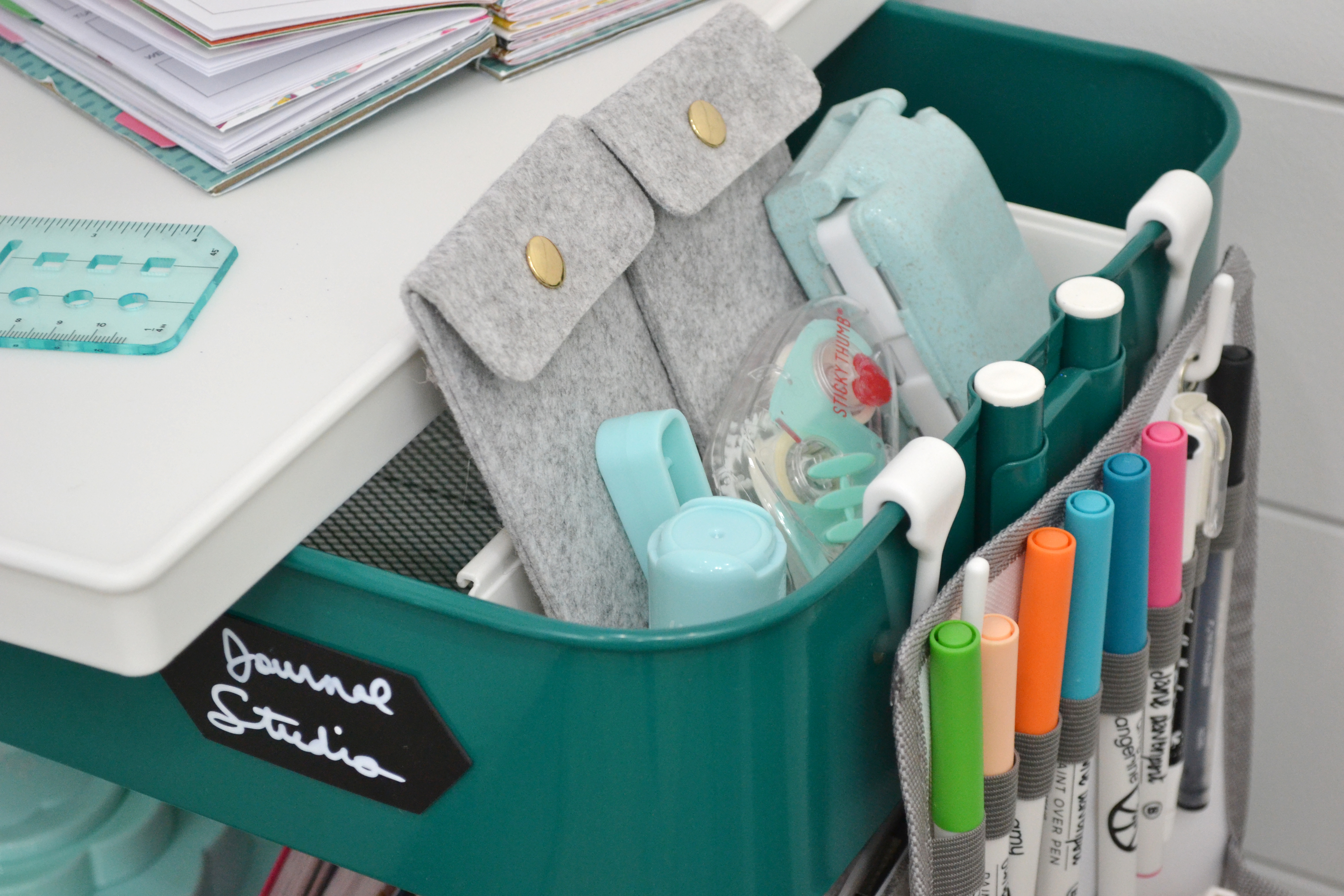 The Cart Pocket from the A La Cart collection allows me to fit so much more on the cart. It fits on the side easily with the included removable hooks. I use it to hold my markers, cutting tools, and some Journal Studio supplies.