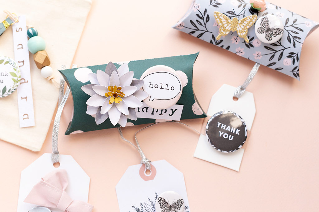 A pillow box with a handmade paper flower, a flair with the word Hello.