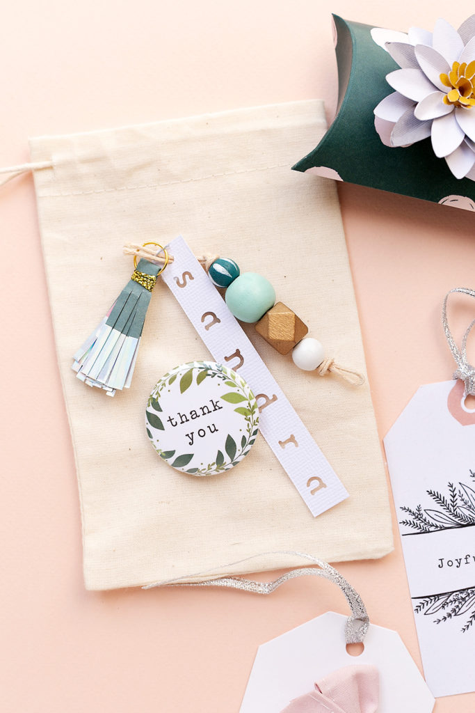 A cotton gift bag with a 'Thank you' button, two tassel embellishments and a tag saying 'Sandra'.