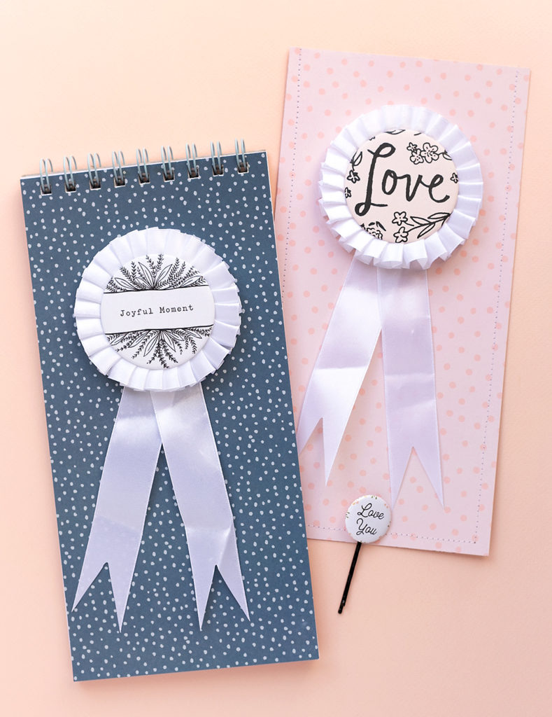 A handmade notebook with a rosette on the cover next to a slip-in-pocket with a rosette saying LOVE.