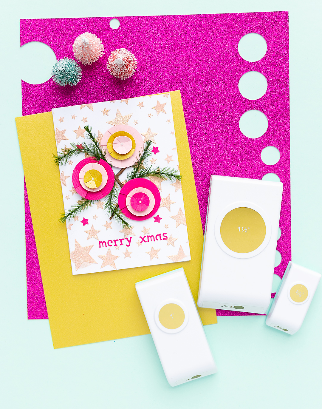 Nesting Punch Circle on gold and glitter paper with a Christmas card and three handmade ornaments.