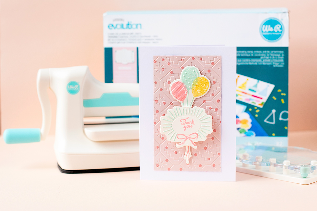 Mini Evolution Die-Cutting Machine with a fancy party card saying Thank you. Add layered stamped details with the stamping press.
