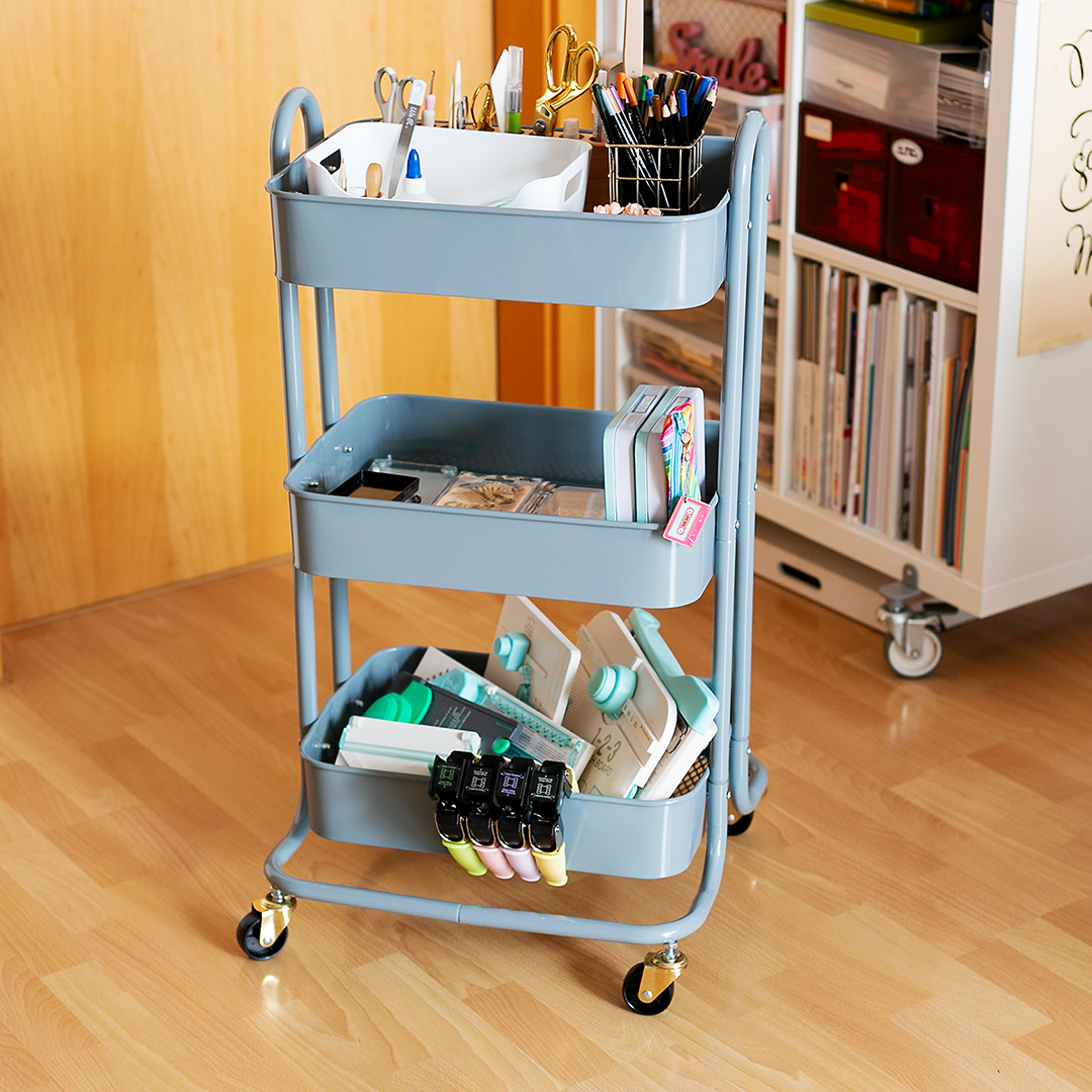 Storage Cart by We R Memory Keepers with three shelves holding craft supplies, punch boards, and tools.