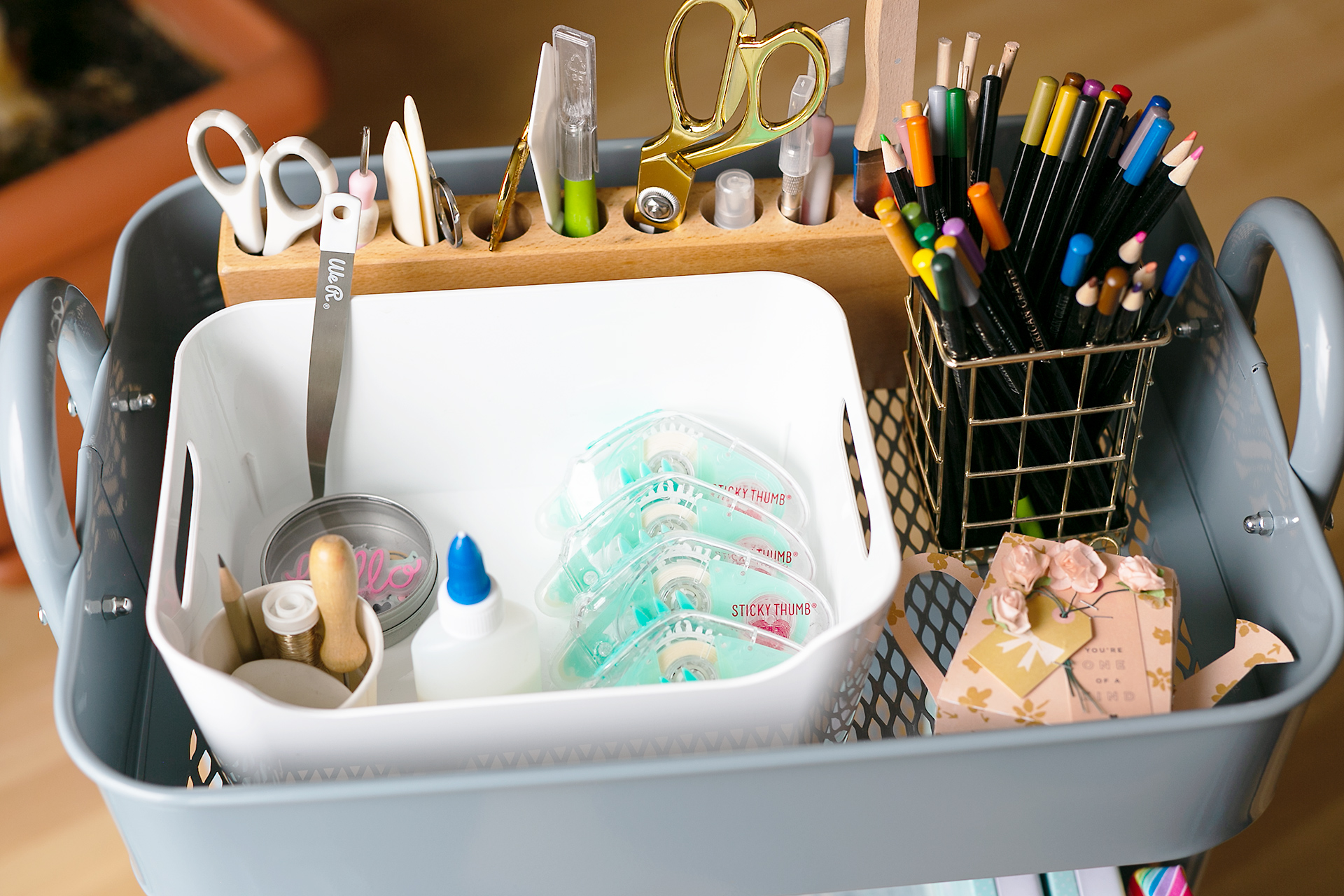 Top shelve of the steel blue storage card by WRMK. A white container holds glue, tape runners, and other small items. On the right side, there is a golden pencil holder. A wooden storage for pencils hold scissors, bone folders, and other helpers.