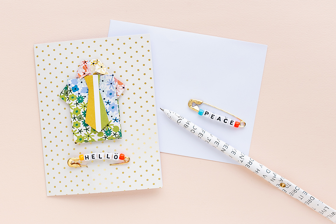 A card with golden dots and a shirt with tie. An alphabet pin from Jen Hadfield saying Peace lies on an envelope along with a pen.