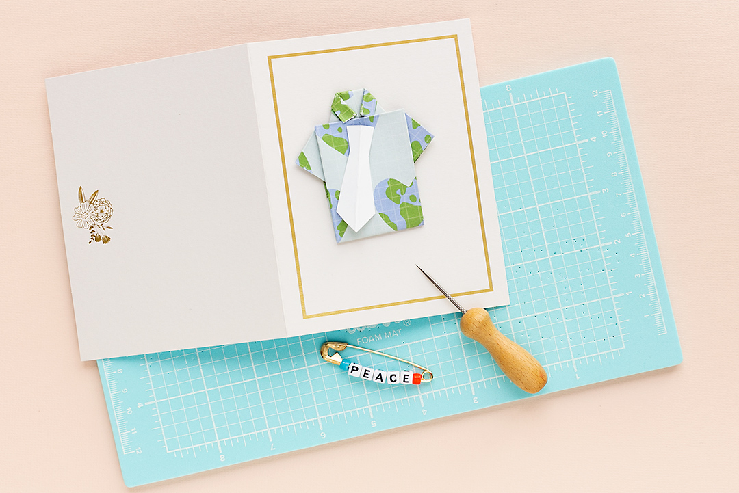 A card with a shirt and a tie on a WRMK foam mat. Pierce holes into the card base to attach the alphabet pin.