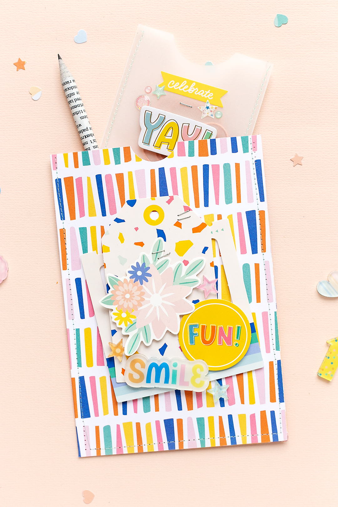 A party goodie bag with a fun pattern and layered embellishments from the papercrafting and scrapbooking collection Buenos Dias by Obed Marshall. The bag is stuffed with a pencil and a handmade vellum bag.